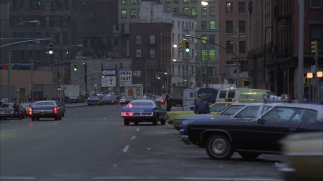 downtown     nyc traffic police car follows white van around corner - 1977 stock videos & royalty-free footage