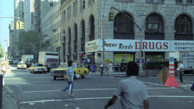 """camera pans ny street traffic and buildings   cmi to hammer's office window see drug store on street corner the drug store is on street level   says """"drugs""""  duane reade - 1986 stock videos & royalty-free footage"""