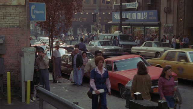 wide shot of ford mustang in heavy city traffic   neg cut see police officer in bg writing tickets newsstand news stand - 1986 stock videos & royalty-free footage