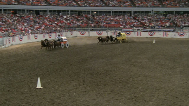 day -- interior astrodome chuckwagon race -- rodeo head trim spectators stands people / camera pans up to principals they sit down and speak with another man wearing a cowboy hat entering stadium crowds. - rodeo stock videos & royalty-free footage