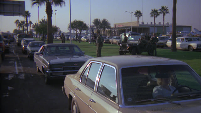 cars stopped at stand still on road street freeway highway / camera pans r to see soldiers jeeps guns on lawn grass / palm trees in the bg / see airport terminal / airplanes in bg / airport access road - 1978 stock videos & royalty-free footage