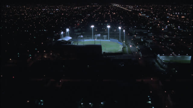 aerial of illuminated baseball field at night. see city lights surrounding baseball field. could be miami. pov circles around field. - baseball diamond stock videos & royalty-free footage