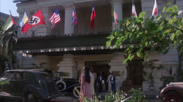 "est shot   "" raffles hotel "" see 46-d     ip period hotel / entrance to upper class hotel with doorman / flags over door american flag nazi flag british flag korean flag / people walking on the streets / 1940's cars and attire - 1938 stock videos & royalty-free footage"