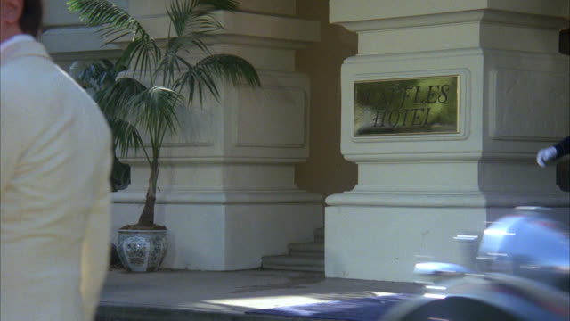 "entrance to upper class asian hotel "" raffles hotel people    cars    rickshaw period hotel / older 1920's cars drive by / palm trees - 1938 stock videos & royalty-free footage"