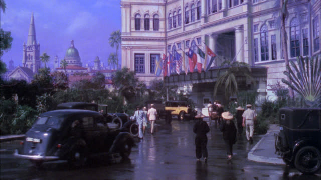 "matte shot    "" raffles hotel "" high class  period hotel / upper class hotel with flags hanging over entrance american flag nazi flag british flag korean flag / activity in front of hotel people rickshaws` - 1938 stock videos & royalty-free footage"