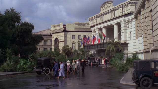 raffles hotel      for matte period hotel / upper class hotel with flags hanging over entrance american flag nazi flag british flag korean flag / activity in front of hotel people / 1940's cars and attire / matching r790-5 r790-6 r790-7 r790-9 - 1938 stock videos & royalty-free footage