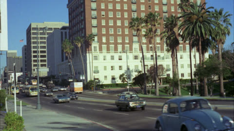 """stockvideo's en b-roll-footage met est """" sheraton west hotel """"     traffic passes in front    nd hotel older red brick 8 to 10 floors with parking lot in fg   palm trees visible / 1970's cars on city streets city buses / see office buildings in bg - zuidelijk californië"""