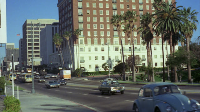"est "" sheraton west hotel ""     traffic passes in front    nd hotel older red brick 8 to 10 floors with parking lot in fg   palm trees visible / 1970's cars on city streets city buses / see office buildings in bg - 1975 stock videos & royalty-free footage"
