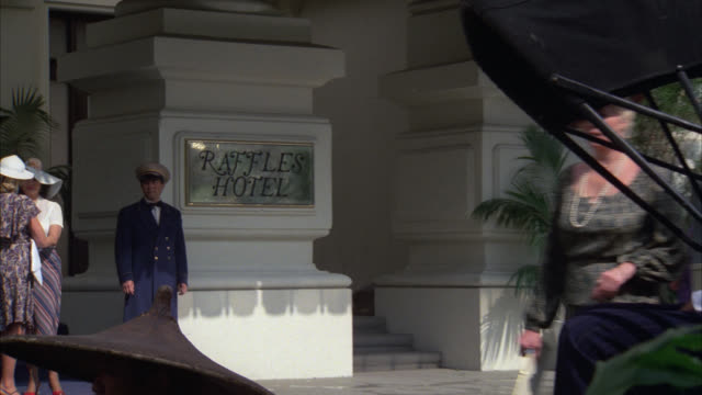 "close on "" raffles hotel ""    cpb cars in  period hotel / people activity in front of hotel / rickshaw / entrance / upper class - 1938 stock videos & royalty-free footage"