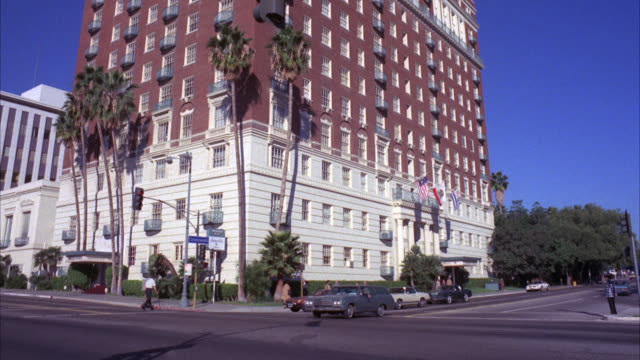 vídeos de stock e filmes b-roll de est sheraton hotel from across the street / middle class / high rise / brick / palm trees in fg / city street with light traffic in fg / matching r791-1 r791-2 - 1976