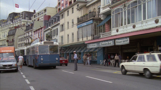 """ble trolley car by l-r      sign on trolley reads """" villeneuve """"        pan up to brick hotel sign """" hotel splendid """"    about five stories foreign / city streets / traffic / street cars / city buses / commercial area / stores storefronts / hotel splendid - 1985年点の映像素材/bロール"""