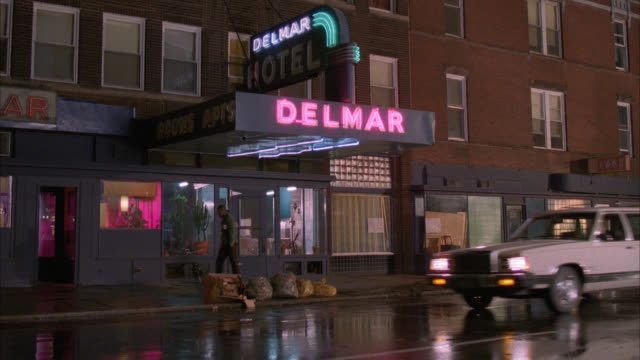 est delmar hotel  del mar four story red brick low class static shot with wet street and trash on sidewalk match matching dx is 1202-i / lower class / neon sign over door entrance / light city traffic and few pedestrians in fg - 1985 stock videos & royalty-free footage
