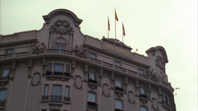 up angle to the ritz hotel  camera pulls back  see traffic on barcelona city street  fairly busy foreign city / flags on top of hotel / lots of city traffic cars in front of hotel city bus / fountain / upper class - 1992 stock videos & royalty-free footage