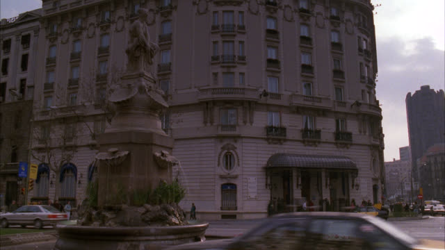 establish ritz hotel in barcelona with fountain and statue in fg  see foreign looking taxi cab out front passes for hotel in any nd non descript foreign city  static shot with much traffic   closer angle on the hotel is 1380-e / upper class - 1992 stock videos & royalty-free footage