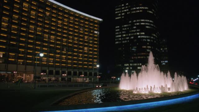 est century plaza hotel with light traffic by in foreground / fountain lit in fg / office buildings in bg / hotel lights and streets lights are on / entrance / matching r793-7 r793-8 - 1993 stock videos & royalty-free footage