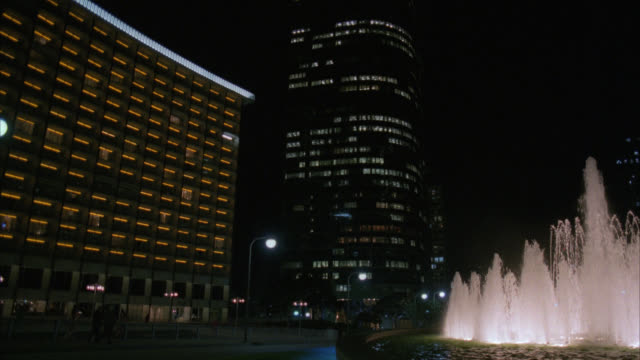 est century plaza hotel with light traffic by in foreground / fountain lit in fg / office buildings in bg / hotel lights and streets lights are on / entrance / matching r793-7 r793-8 - century city stock videos & royalty-free footage
