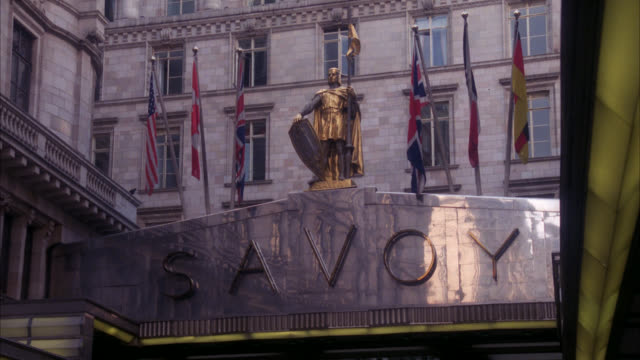 est the savoy hotel  up angle to stone sign   neg is cut at pan down to street foreign / statue and flags on top of over entrance / british flag american flag canadian flag / upper class / neg cut / rolls royce and other cars parked in front - stereotypically upper class stock videos & royalty-free footage
