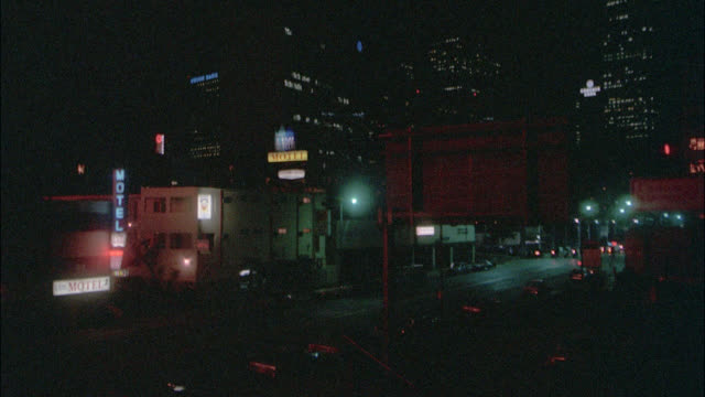 """ls on city street    hotel on left    fire chief's car runby r-l    two fire trucks enter right following / very dark / see neon sign """"hotel"""" and street lights / office buildings downtown skyscrapers with some lights on in bg - downtown stock videos & royalty-free footage"""