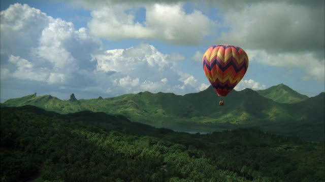 aerial of colorful hot air balloon floating above tropical island. see green foliage or growth below. see gray clouds in sky. note: neg is cut at 236-267 mow basket brushes tree tops as it rises - island stock videos & royalty-free footage