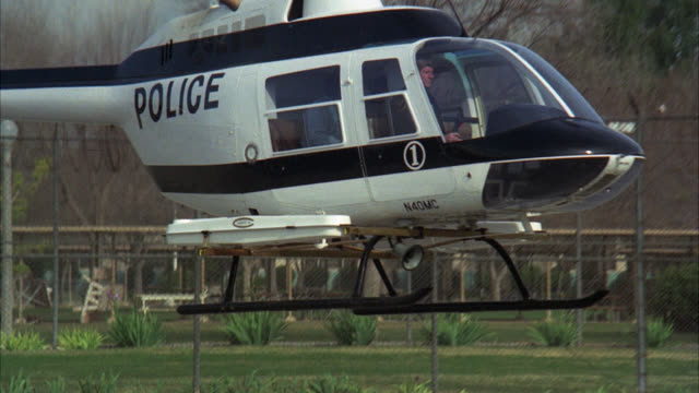 vidéos et rushes de pan r-l to follow man prisoner inmate running to blue and white police helicopter / gets in chopper / police helicopter takes off / prison / prison yard / chain link fence with barbed wire - hélicoptère