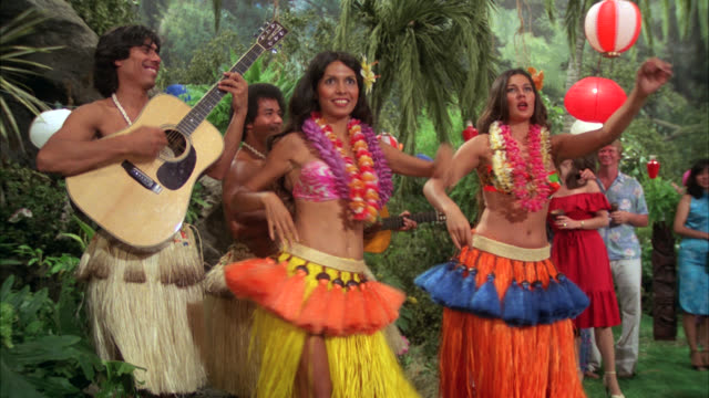 luau dance    natives and other people scenic with torches    scene starts on dancing girls hips     luau / colored colorful grass skirts / lanterns / - minoranza video stock e b–roll