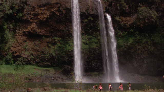 double waterfalls     five native hawaiian girls in fg at lake / girls wear wreathes and carry flowers /  tropical island landscape / matching r1156-7 r1156-8 r1156-10 - wreath stock videos & royalty-free footage