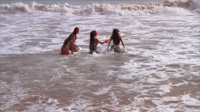 cove    four native hawaiian girls stand hand in hand at waters edge      they run bg in to surf jumping small waves etc    they run out camera left hawaiians - 1978 stock videos & royalty-free footage