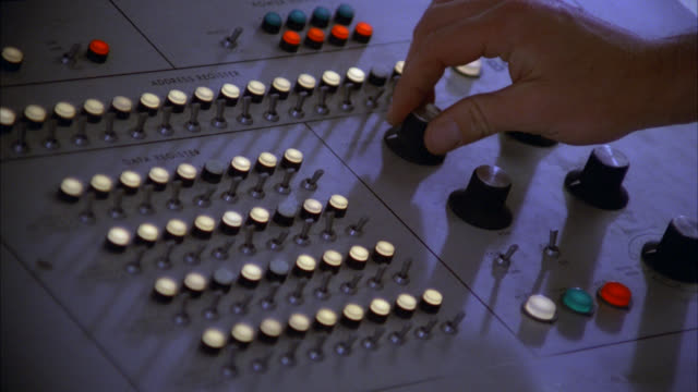 stockvideo's en b-roll-footage met ecu shot from above -  vintage 1970's 1980's computer console insert of hands typing turning knobs pushing buttons keys levers switches  [shots 1230-01 to 1231-01 match] - regelkamer