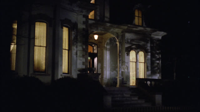 wide angle of victorian gothic white three story mansion house at night. see inside lights on. - 1992 stock videos & royalty-free footage