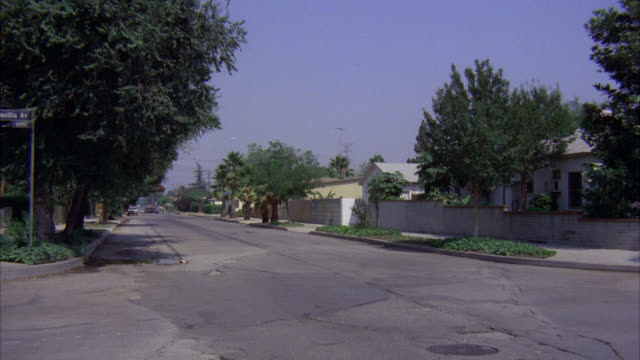 est residential area neighborhood tree lined streets one story houses lower middle class / chase l-r makes left turn [shots 1311-01 to 02 and 1312-02 match] - southern california stock videos & royalty-free footage