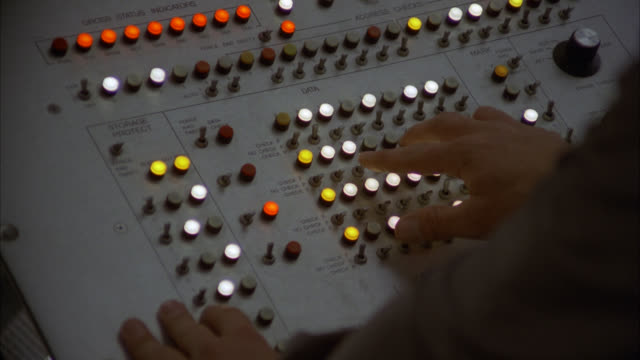 stockvideo's en b-roll-footage met shot from above pov over the shoulder -  vintage 1970's 1980's computer console insert of hands typing turning knobs buttons keys levers switches [shots 1230-01 to 1231-01 match] - regelkamer