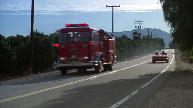pov out of side of country road tree lined road pans l-r  of corvette fire truck speeding by r-l multiple takes - 消防車点の映像素材/bロール