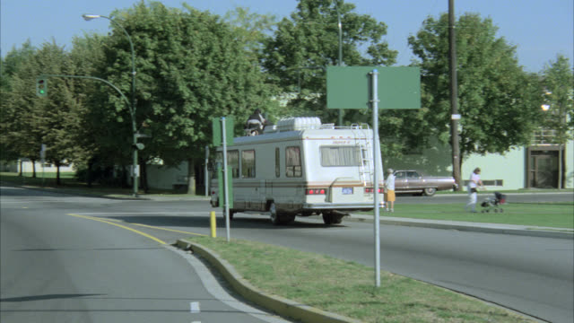 stockvideo's en b-roll-footage met park from across the street picnic  city park     see one person sitting on park bench  green grass trees winnebago rv enters from r to lf with two men on roof pulls to stop light and does three point turn with old woman on corner and joggers cross street - 1985