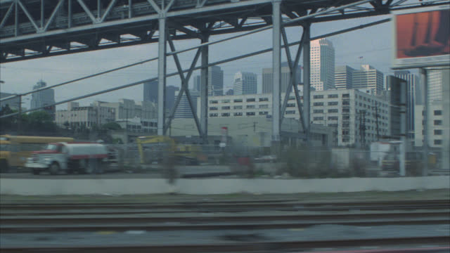 vídeos de stock, filmes e b-roll de 5/8 left      embarcadero    process plate / passing by downtown / warehouses / train tracks in fg bridge / city skyline in bg - placa de processo