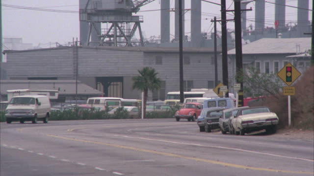wide angle of street near los angeles harbor area traffic to camera     pan right to follow    see ship in bg. cadillacs, vans, volkswagen, ford ltd sedan drive past camera. - anno 1975 video stock e b–roll
