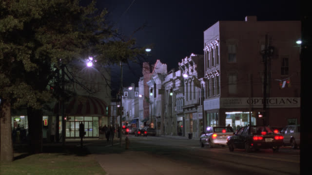vídeos y material grabado en eventos de stock de pan left to right of main street at night with moderate activity. cars in fg. see office building with ornate entrance could be apartment building. lights on in a few windows - señal de nombre de calle