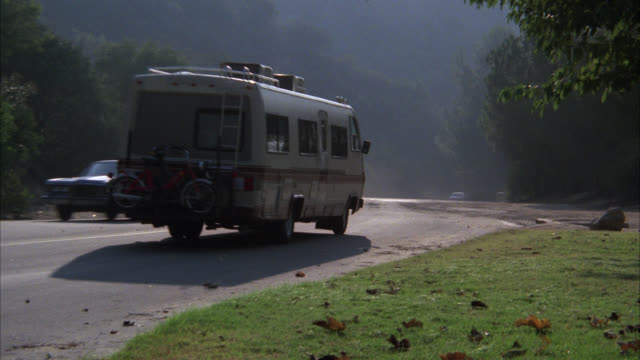 motorhome l-r   away from cam    bump in road mountain roads    recreation vehicle rv motor home - holprig stock-videos und b-roll-filmmaterial