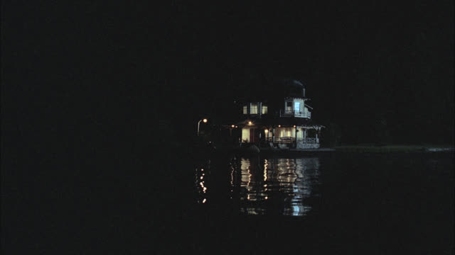 nx est cabin or lodge or house boathouse boat house lake house  2 story on lake with dock and all lights on in house  pov from boat approaching the house cmi to dock  matches matching match dx is 1333-f 1333-h - lake stock videos & royalty-free footage