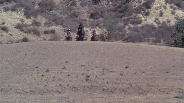 stockvideo's en b-roll-footage met cam follows principals on horseback coming towards fg / opening field area / trees around / old west / mountains in bg - western usa