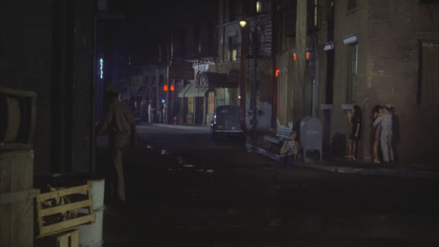 est city street at night lower class run down area with two women prostitutes? on street corner one is with a soldier people walking navy men in uniforms leave bars and walk to camera enlisted men - 1978 stock videos & royalty-free footage