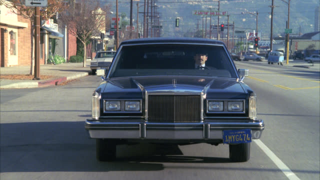 plate looking back to black lincoln towncar limo being driven by chauffeur down victory blvd burbank - limousine stock videos & royalty-free footage