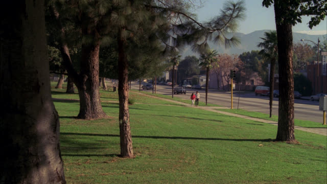 ws est park in city see joggers light traffic on street / cam pans l-r with black lincoln towncar limo being driven by chauffeur down victory blvd burbank - burbank stock-videos und b-roll-filmmaterial