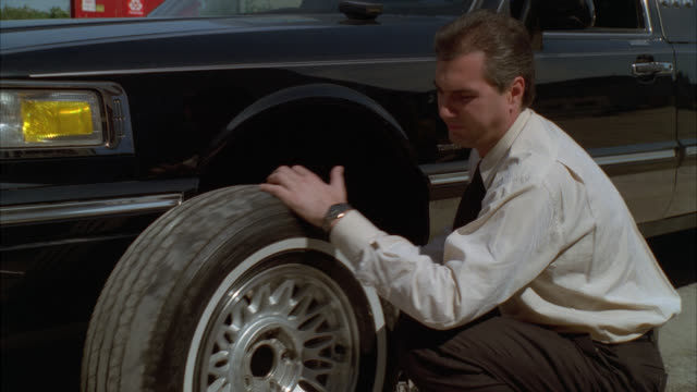 est cu on tire being changed / see man's hands is dressed like chauffeur / black lincoln / multiple takes - chauffeur stock videos & royalty-free footage