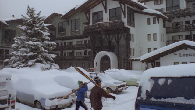 medium angle of multistory white with brown trim ski lodge on snowy day. looks like vail ski resort. see cars in foreground parking lot covered in snow. see coniferous tree at left covered in snow. see pedestrians walk by as snow falls. - ski lodge stock videos & royalty-free footage
