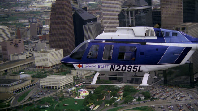 aerial of lifeflight or medical helicopter flying over houston skyline. see various high rise buildings and skyscrapers. see helicopter pull back towards downtown houston. see red cross on bottom of helicopter. - 1987 stock videos & royalty-free footage