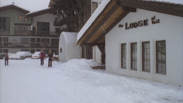 vidéos et rushes de medium angle of multistory white with brown trim ski resort on snowy day. see sign reading the lodge at vail. see skiers walk by as snow falls. - chalet