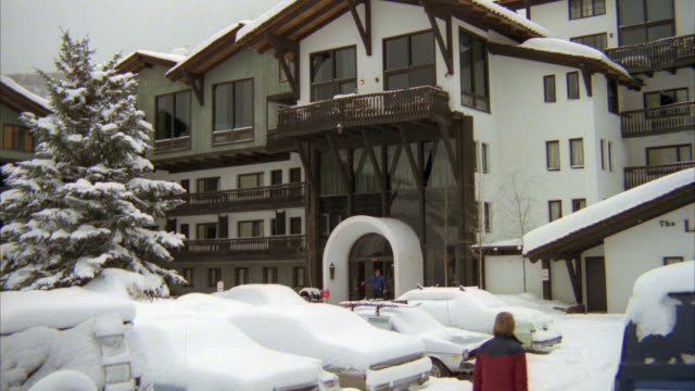 white with brown trim ski lodge on snowy day. looks like vail ski resort. see cars in foreground parking lot covered in snow. see coniferous tree at left covered in snow. see pedestrians walk by as snow falls. zoom in to balcony above entrance. pull back. - ski lodge stock videos & royalty-free footage