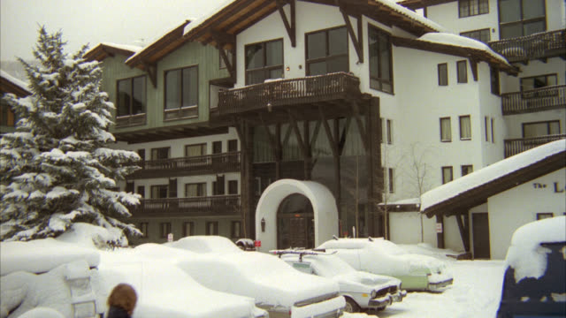 multistory white with brown trim ski lodge on snowy day. looks like vail ski resort. see cars in foreground parking lot covered in snow. see coniferous tree at left covered in snow. see pedestrians walk by as snow falls. zoom in to balcony above entrance. - ski lodge stock videos & royalty-free footage