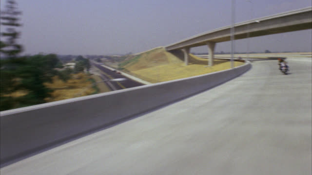 over the shoulder shot of motorcyclist on empty highway / cam pans l-r behind to second motorcycle / see police car far behind / freeway comes to end / see overpasses city / neg cut - 1987 stock videos & royalty-free footage