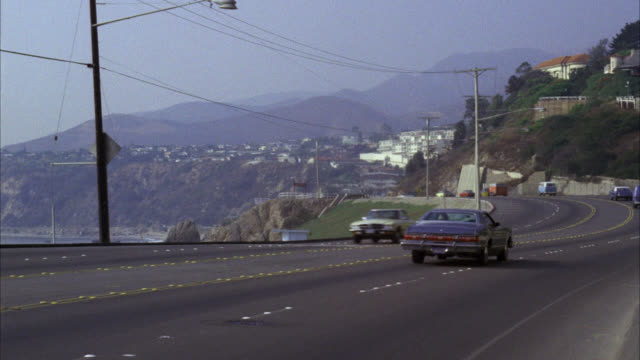 est ws facing south pacific coast highway pch with moderate traffic north of santa monica / see hill on left beach on right / cam pans l-r with large 2 door 1970's blue sedan / neg cut to same shot facing north cam pans r-l with same sedan - california stock videos & royalty-free footage